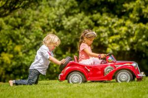 boy pushing girl in a cart